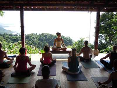 group of people meditating on a wooden yoga deck