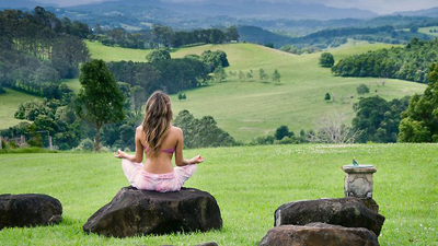 woman meditating in a green field