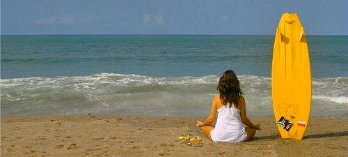 woman with a surfing board meditating