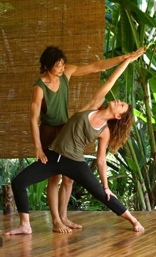 An instructor is helping a woman to hold a yoga pose